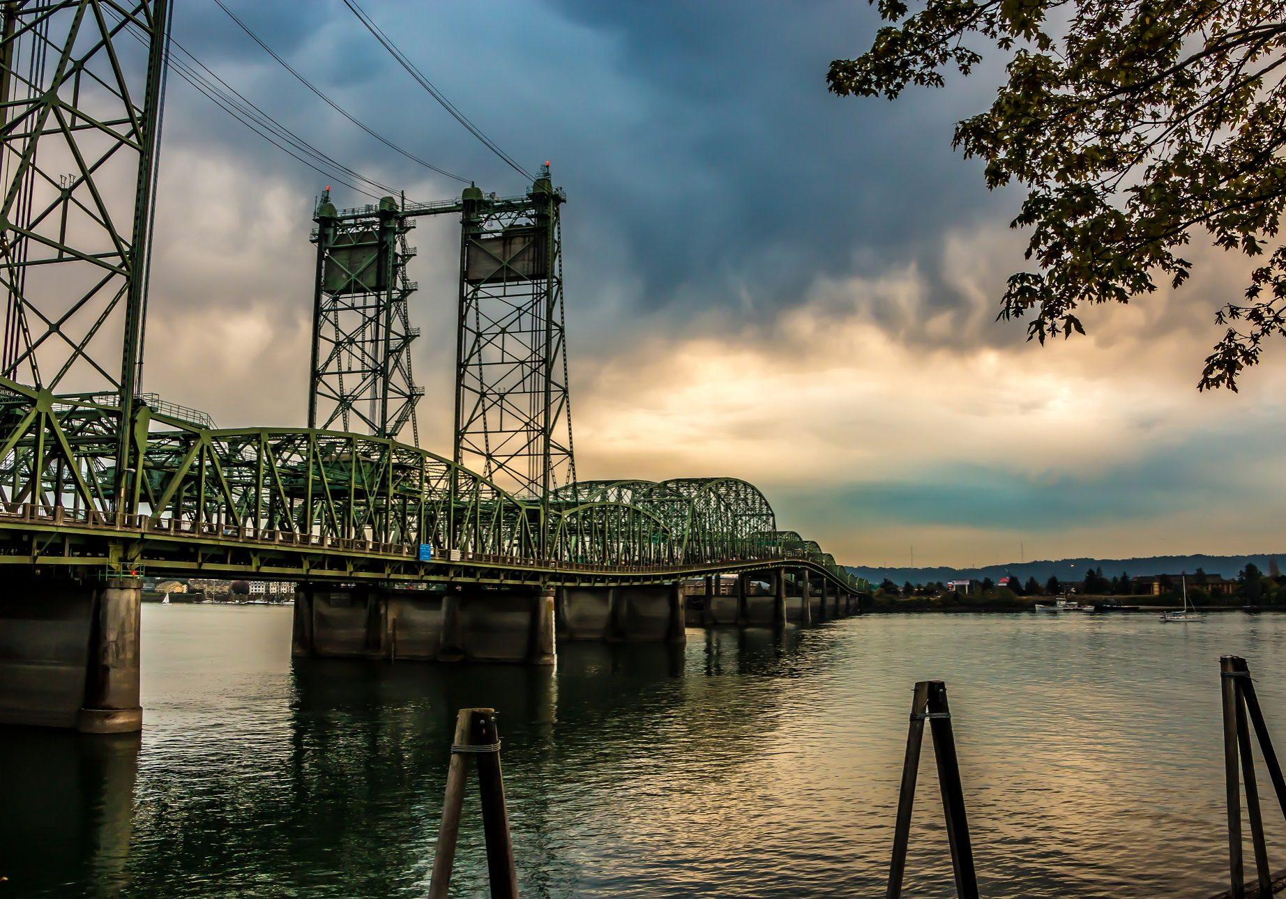 Colorful Sunset Over Columbia River Oregon Washington Bridge Dense Clouds